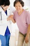 L'infirmière dans la maison de repos aidant la femme supérieure se lèvent Image stock