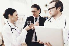 L'infirmière dans la robe de médecine donne le verre de l'eau à l'homme d'affaires qui a le mal de tête photographie stock