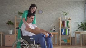 L'infirmière de fille aide dans la réadaptation d'un handicapé dans un fauteuil roulant banque de vidéos