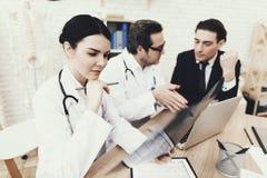 L'infirmière de jeunes examine le rayon X au bureau médical Docteur et patient brouillés à l'arrière-plan photographie stock libre de droits