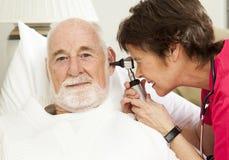 L'infirmière de santé à la maison contrôle des oreilles Photos libres de droits