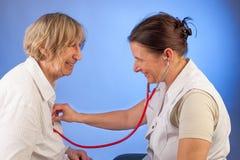 L'infirmière examine la femme agée avec le stéthoscope Photo libre de droits