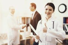 L'infirmière heureuse dans la robe de chambre médicale avec le stéthoscope et le dossier montre le pouce  photo stock