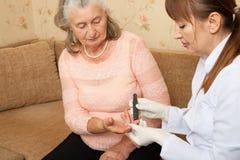 L'infirmière passe l'examen pour le sucre dans le sang des personnes âgées Photographie stock libre de droits