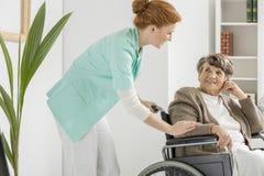 L'infirmière rend visite à l'aîné handicapé Image stock