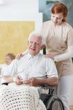 L'infirmière se tient à côté d'un homme plus âgé Images libres de droits