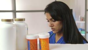 L'infirmière prenant l'inventaire de drogue sourit à l'appareil-photo clips vidéos