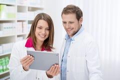 L'information de contrôle de deux pharmaciens sur un comprimé Photo stock