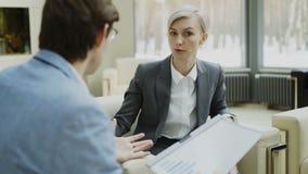 L'information parlante et duscussing de femme d'affaires de société de finances avec l'associé masculin s'asseyant sur le fauteui