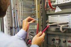 L'ingénieur d'électricien avec le multimètre examine le panneau de commande électrique de l'équipement d'automation Spécialiste d photos stock