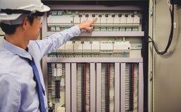 L'ingénieur d'électricien examine le panneau de commande électrique de centrale d'installations photos stock