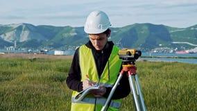 L'ingénieur d'arpenteur mesure de niveau sur le chantier de construction Geodesist assurent des mesures précises avant d'entrepre clips vidéos
