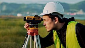 L'ingénieur d'arpenteur mesure de niveau sur le chantier de construction Geodesist assurent des mesures précises avant d'entrepre banque de vidéos