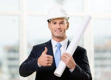 L'ingénieur dans le casque antichoc remet la disposition et les pouces vers le haut Photographie stock libre de droits