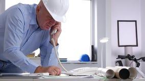 L'ingénieur dans un bureau de conception font un entretien d'appel téléphonique utilisant une ligne terrestre technique banque de vidéos