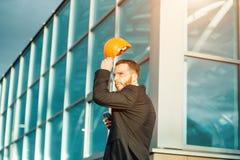 L'ingénieur de constructeur porte le casque ou le tient dans des mains sur le fond de la construction photographie stock