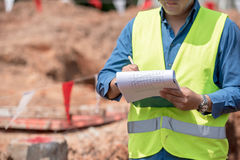 L'ingénieur en plein pendant le disque de note pour inspectent le chantier de construction Photographie stock libre de droits