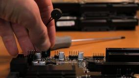 L'ingénieur enlève le haut-parleur de la carte mère banque de vidéos
