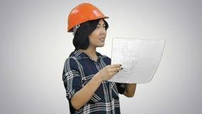 L'ingénieur féminin avec un hemlet de jrange et la construction prévoient l'essai de parler avec quelqu'un loin sur le fond blanc clips vidéos