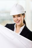 L'ingénieur féminin dans le casque antichoc remet le croquis Photographie stock libre de droits