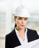 L'ingénieur féminin dans le casque antichoc remet le modèle Image libre de droits