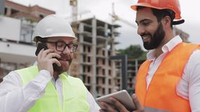 L'ingénieur heureux parle du téléphone portable sur le chantier de construction et vérifie le travail du travailleur Entretiens d banque de vidéos