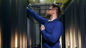 L'ingénieur masculin essaye de brancher un câble aux serveurs banque de vidéos