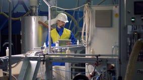 L'ingénieur masculin inspecte les bouteilles en plastique en mouvement banque de vidéos