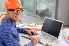 L'ingénieur masculin mûr habile travaille dans le bureau Image stock