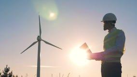 L'ingénieur masculin tient un ordinateur portable, des types là-dessus et des moulins à vent électriques de contrôles Electririty banque de vidéos