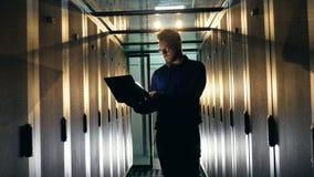 L'ingénieur masculin travaille avec son ordinateur portable, vérifiant l'équipement de serveur Spécialiste en degré de sécurité d clips vidéos
