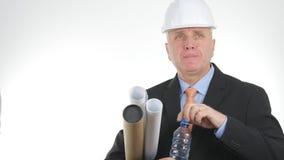 L'ingénieur With Plans dans des mains boivent l'eau douce d'une bouteille photos stock