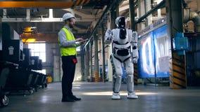 L'ingénieur professionnel commande un robot, dactylographiant sur un comprimé clips vidéos