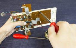 L'ingénieur répare le panneau de puce avec un tournevis photographie stock