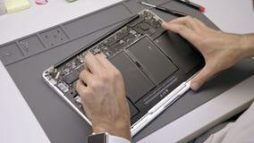 L'ingénieur répare l'ordinateur portable endommagé pareau La batterie d'extrait d'ingénieur de l'ordinateur portable banque de vidéos