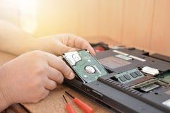 L'ingénieur reconstitue le PC d'ordinateur portable Installation du matériel d'unité de disque dur, RAM Atelier de réparations él Photos stock
