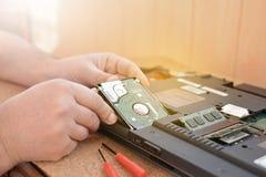 L'ingénieur reconstitue le PC d'ordinateur portable Installation du matériel d'unité de disque dur, RAM Atelier de réparations él Photos libres de droits