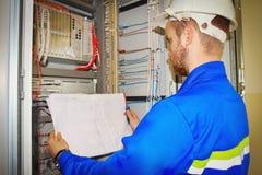 L'ingénieur regarde le dessin électrique sur le fond du panneau d'automation photographie stock libre de droits