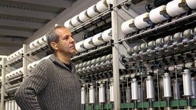 L'ingénieur regarde les machines dans l'usine de textile Photos stock