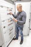 L'ingénieur travaille dans l'armoire d'alimentation Photographie stock