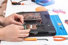 L'ing?nieur fait le d?montage de RAM pour d?monter et r?parer un ordinateur portable images libres de droits