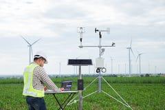 L'ingegnere che per mezzo del computer della compressa raccoglie i dati con meteorologico fotografie stock