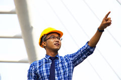 L'ingegnere con il cappello di sicurezza sta indicando Fotografie Stock