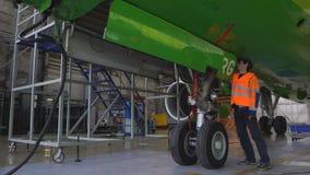 L'ingegnere controlla il funzionamento della covata del carrello di atterraggio anteriore degli aerei video d archivio