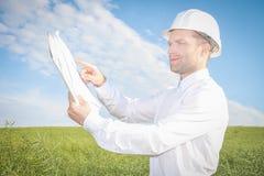 L'ingegnere dell'architetto indica i disegni della documentazione del progetto al sito di costruzione della proprietà Fotografia Stock Libera da Diritti
