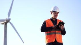 L'ingegnere dell'aspetto caucasico in un casco e la maglia guardano il lavoro del mulino a vento, esaminante la compressa archivi video