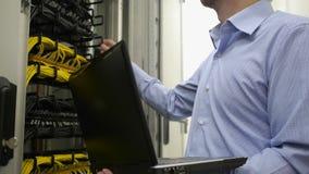 L'ingegnere dell'IT controlla lo scaffale del server stock footage