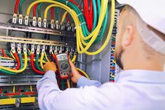 L'ingegnere dell'elettricista misura la tensione con il multimetro in gabinetto ad alta tensione Fotografie Stock