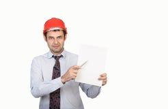 L'ingegnere dell'uomo in un casco rosso mostra la sua penna fotografia stock