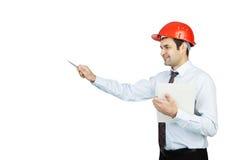 L'ingegnere dell'uomo in un casco rosso mostra la sua penna fotografie stock